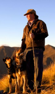 Image of Lloyd Smith in the hills with his dogs