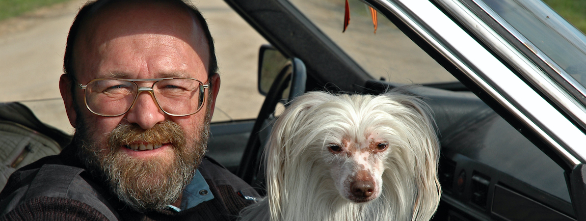 Man Holding White Fluffy Dog Sitting In A Car