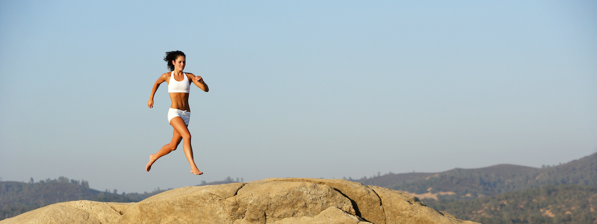 Image Of A Woman Running Over Large Rocks