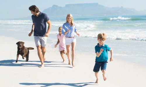 A Healthy Family And Their Dog Running On The Beach.